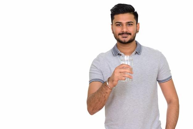 Junger schöner indischer mann, der glas wasser hält