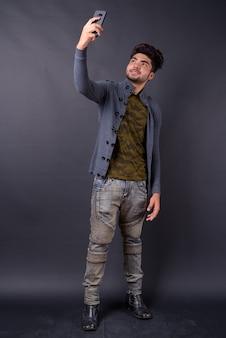 Junger schöner indischer mann gegen schwarzen hintergrund