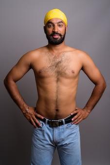 Junger schöner indischer mann hemdlos auf grauem hintergrund