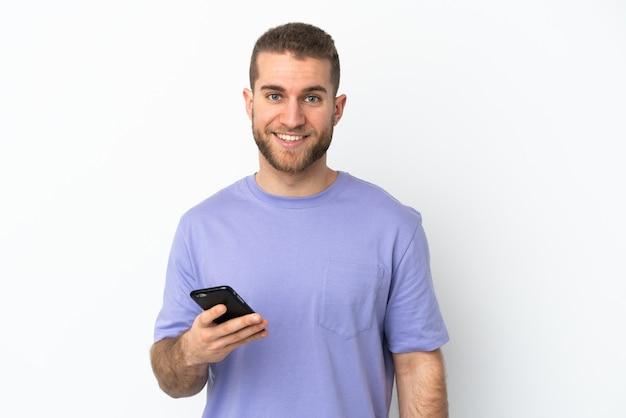 Junger schöner kaukasischer mann lokalisiert auf weißem hintergrund unter verwendung des mobiltelefons