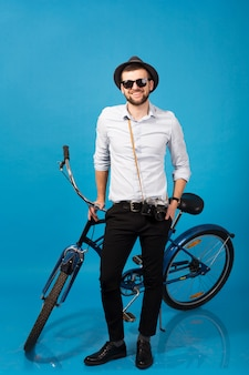 Junger schöner lächelnder glücklicher mann, der auf hipster-fahrrad reist, das auf blauem studiohintergrund aufwirft, hemd, hut und sonnenbrille tragend