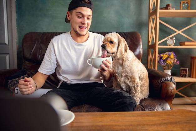 Junger schöner mann, der auf braunem sofa sitzt und mit seinem niedlichen hund arbeitet