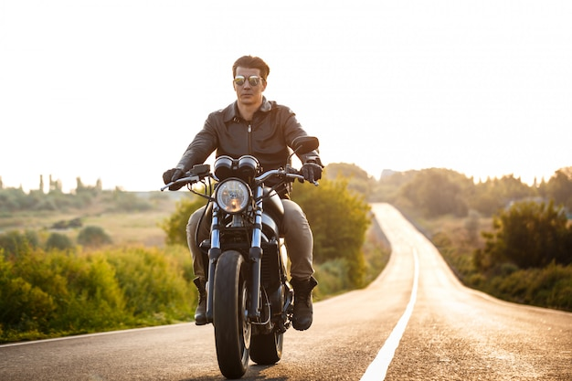 Junger schöner mann, der auf motorrad an landstraße reitet.