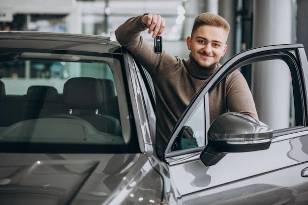 Junger schöner mann, der ein auto in einem autoausstellungsraum wählt