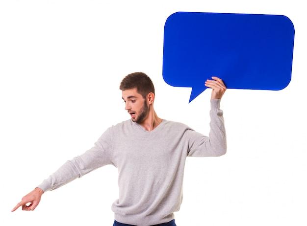 Junger schöner mann, der eine blaue luftblase für text anhält.