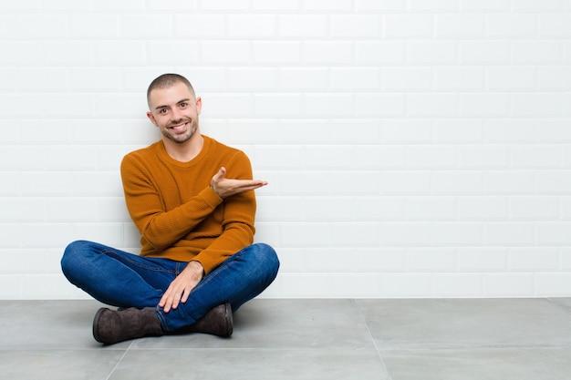 Junger schöner mann, der fröhlich lächelt, sich glücklich fühlt und ein konzept im kopierraum mit handfläche zeigt, die auf dem boden sitzt
