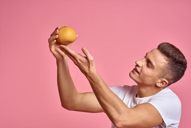Junger schöner mann, der früchte lokalisiert hält