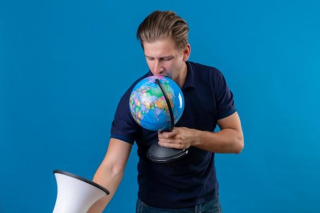 Junger schöner mann, der globus und megaphon hält, die spielerisch und glücklich stehen über blauem hintergrund stehen