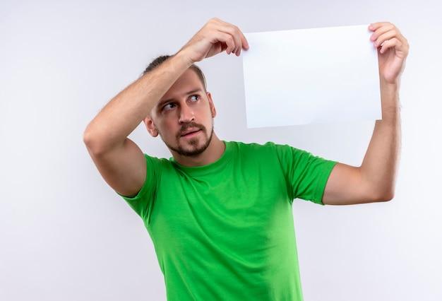 Junger schöner mann, der grünes t-shirt hält, das leeres papier hält, das es fasziniert, über weißem hintergrund stehend betrachtet