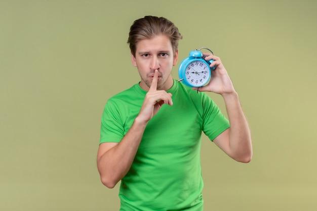 Junger schöner mann, der grünes t-shirt hält, das wecker hält, der stille geste mit finger auf den lippen macht, die über grüner wand stehen