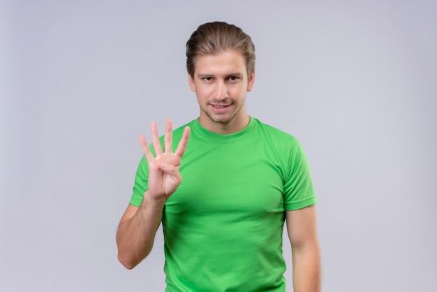 Junger schöner mann, der grünes t-shirt trägt, das mit den fingern nummer drei zeigt und zeigt