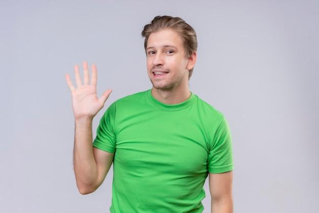 Junger schöner mann, der grünes t-shirt trägt, das vertraulich schaut und lächelt