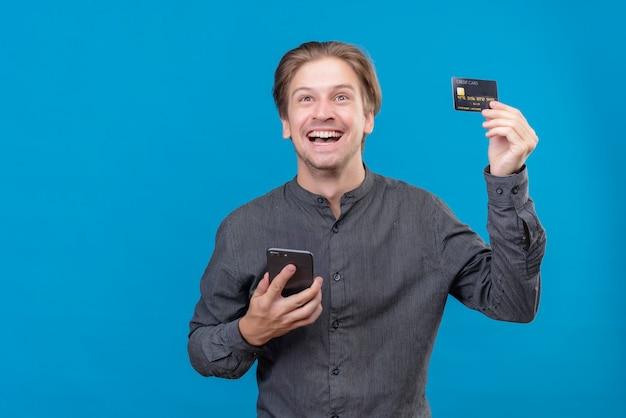 Junger schöner mann, der handy und kreditkarte hält