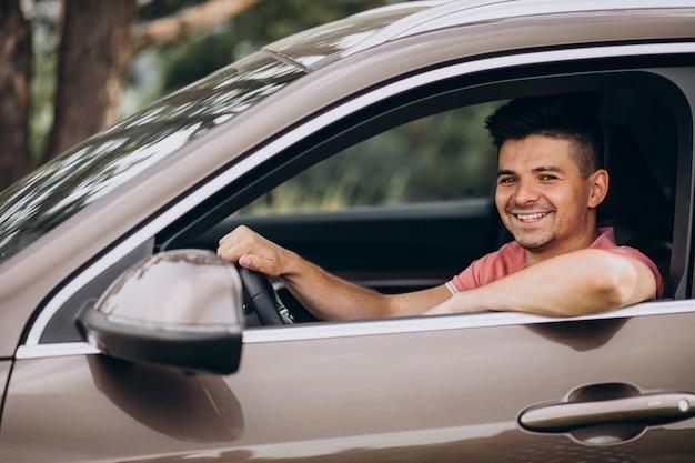 Junger schöner mann, der im auto sitzt