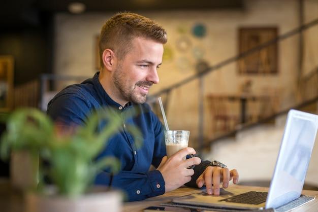 Junger schöner mann, der kaffee trinkt, während laptop im café verwendet wird