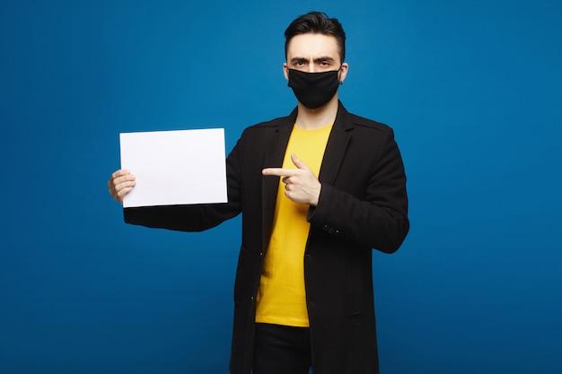 Junger schöner mann, der leeres blatt papier hält, lokalisiert am blauen hintergrund. junger mann, der auf ein blatt des papierblatts zeigt und in die kamera schaut. werbekonzept