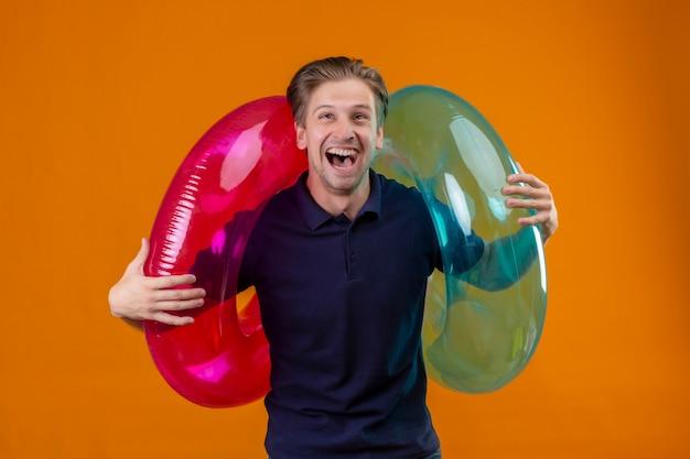 Junger schöner mann, der mit aufblasbaren ringen steht, überrascht und glücklich mit weit offenem mund über orange hintergrund