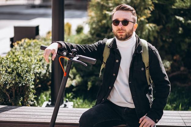 Junger schöner mann, der mit roller im park sitzt