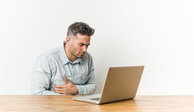 Junger schöner mann, der mit seinem laptop krank arbeitet, unter magenschmerzen leidet, schmerzhaftes krankheitskonzept.