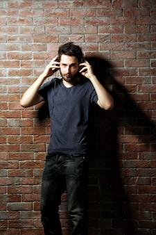 Junger schöner mann, der musik mit kopfhörern auf backsteinmauerhintergrund hört