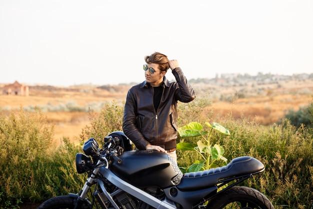 Junger schöner mann, der nahe seinem motorrad an der landstraße aufwirft.