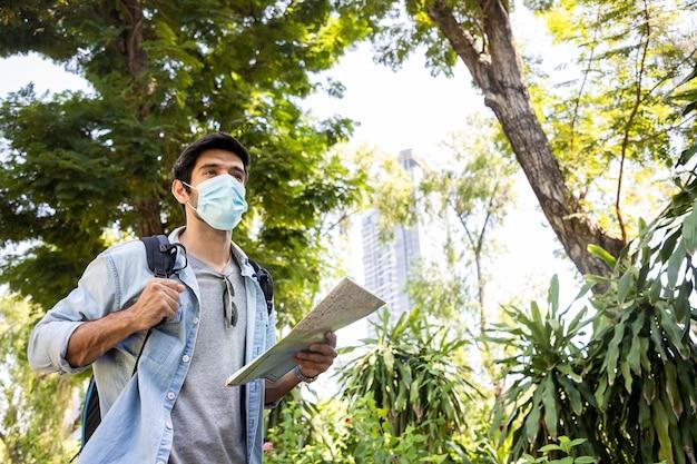 Junger schöner mann, der papierkarte schaut und sonnenbrille im öffentlichen park mit einem glücklichen gesicht steht und lächelt