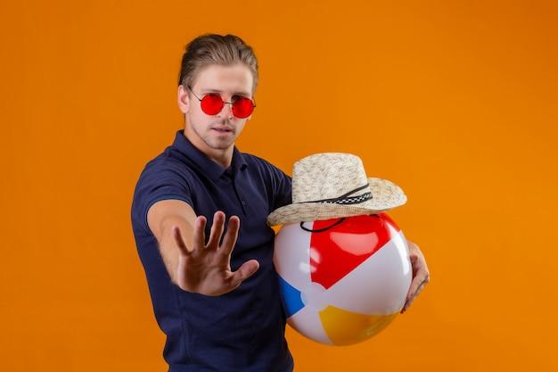 Junger schöner mann, der rote sonnenbrille hält, die aufblasbaren ball und sommerstrohhut hält, der mit offener hand steht, die stoppgeste mit ernstem gesicht über orange hintergrund macht