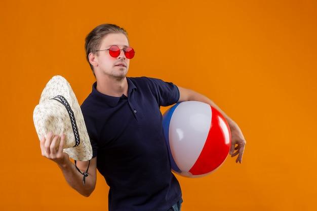 Junger schöner mann, der rote sonnenbrille trägt, die mit aufblasbarem ball steht, der mit strohhut winkt, der über orange hintergrund zuversichtlich schaut