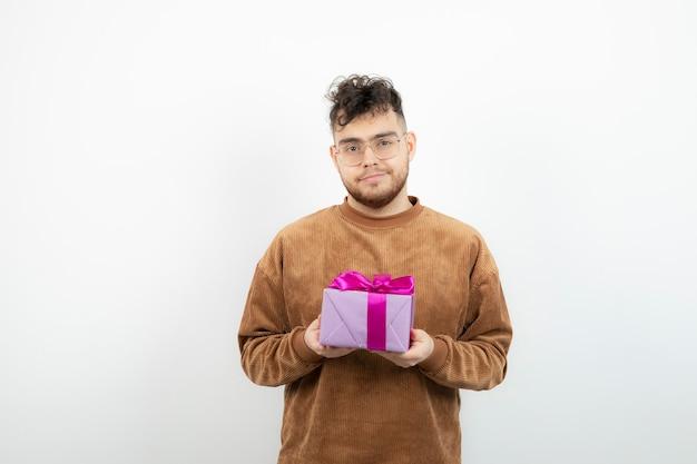 Junger schöner mann, der sein geburtstagsgeschenk über weiß hält.