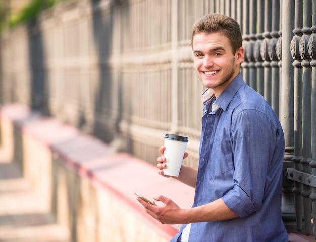 Junger schöner mann, der sein telefon und tasse kaffee hält.