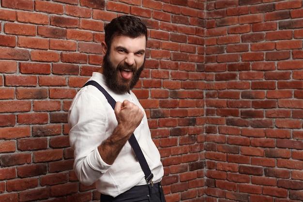 Junger schöner mann, der sich freut, auf ziegelmauer aufwerfend.