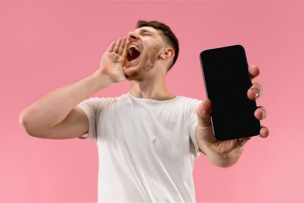 Junger schöner mann, der smartphonebildschirm lokalisiert auf rosa hintergrund im schock mit einer überraschung zeigt