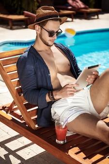 Junger schöner mann, der tablette betrachtet, die nahe schwimmbad sitzt