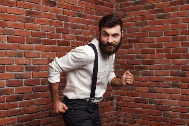 Junger schöner mann, der tanzend auf ziegelmauer tanzt.