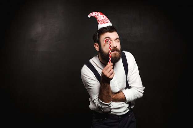 Junger schöner mann, der weihnachtsbonbon über schwarz hält.