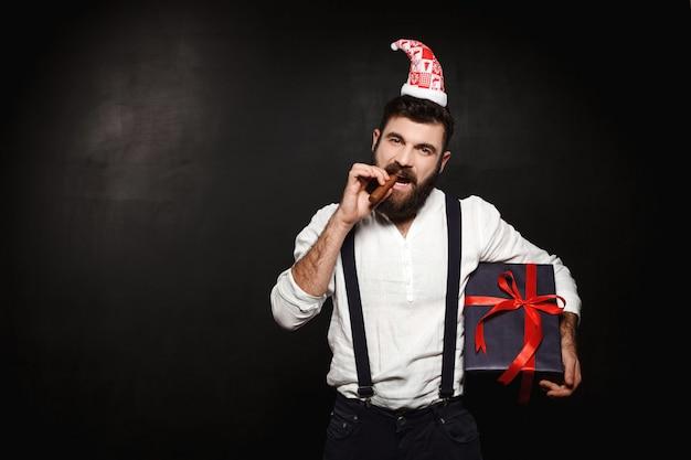 Junger schöner mann, der weihnachtsgeschenkbox über schwarz hält.