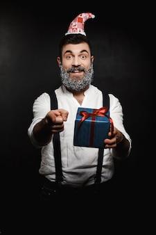 Junger schöner mann, der weihnachtsgeschenkbox zeigt finger zeigt.