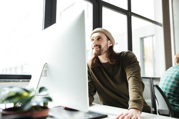 Junger schöner mann im büro unter verwendung des computers