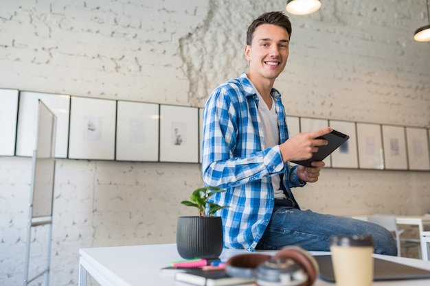 Junger schöner mann im chekered hemd, das auf tisch unter verwendung des tablet-computers im mitarbeitenden büro sitzt