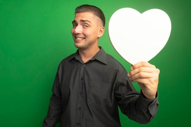 Junger schöner mann im grauen hemd, das kartonherz zeigt, das zuversichtlich lächelt