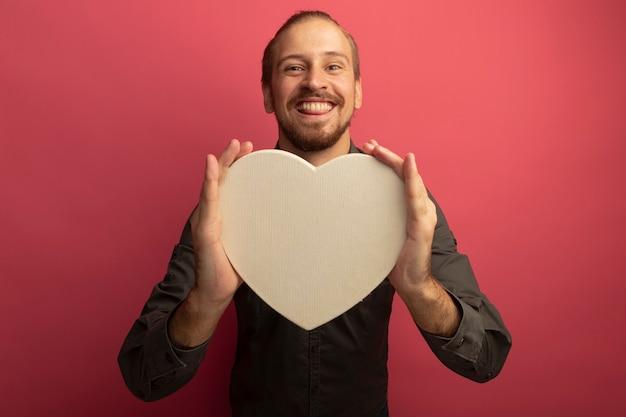 Junger schöner mann im grauen hemd, das pappherz mit großem lächeln auf gesicht hält