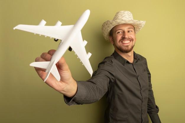 Junger schöner mann im grauen hemd und im sommerhut, der spielzeugflugzeug glücklich und positiv lächelnd fröhlich zeigt