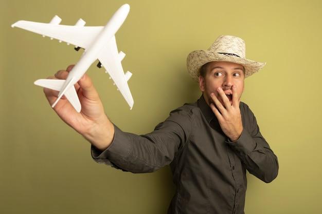 Junger schöner mann im grauen hemd und im sommerhut, der spielzeugflugzeug hält, das es betrachtete, überraschte, mund mit hand bedeckend