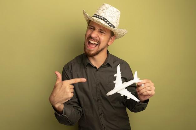 Junger schöner mann im grauen hemd und im sommerhut, der spielzeugflugzeug hält, das mit zeigefinger glücklich und aufgeregt zeigt