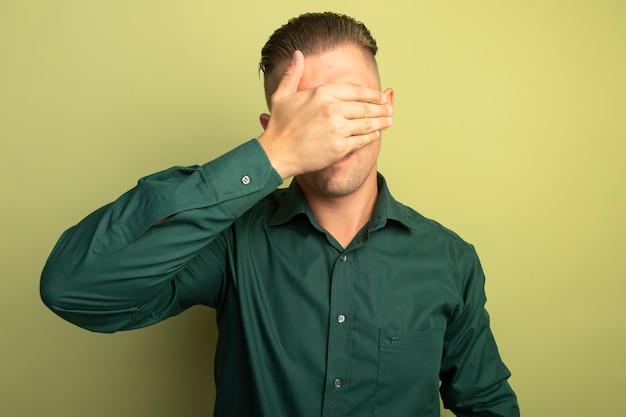 Junger schöner mann im grünen hemd, das augen mit der müden und gelangweilten hand bedeckt, die über heller wand stehen