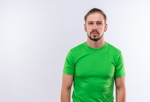 Junger schöner mann im grünen t-shirt, das an der kamera mit ernstem sicherem ausdruck auf gesicht steht, das über weißem hintergrund steht