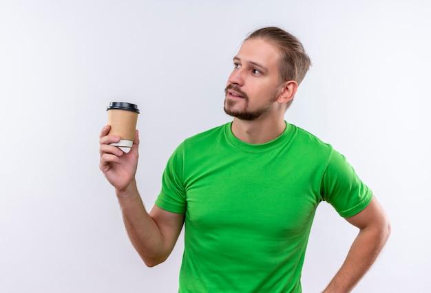 Junger schöner mann im grünen t-shirt, das kaffeetasse hält, die beiseite mit dem sicheren ausdruck auf gesicht steht, das über weißem hintergrund steht