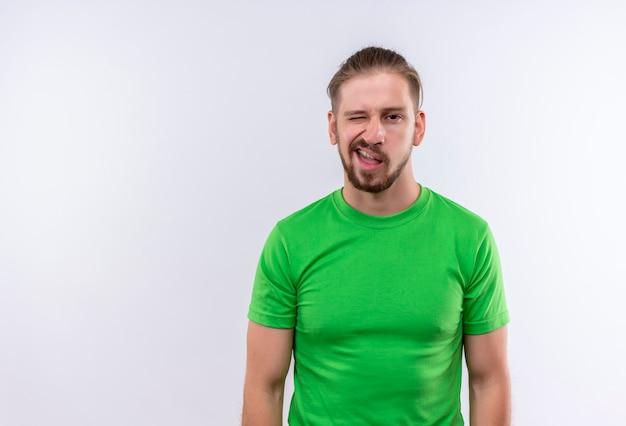 Junger schöner mann im grünen t-shirt, das kamera betrachtet, die grimasse macht, die über weißem hintergrund steht