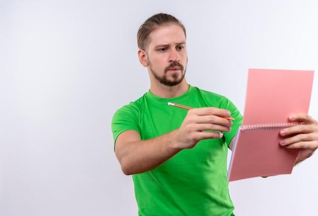 Junger schöner mann im grünen t-shirt, das notizbuch und bleistift hält, das notizbuch mit nachdenklichem ausdruck auf gesicht steht, das über weißem hintergrund steht