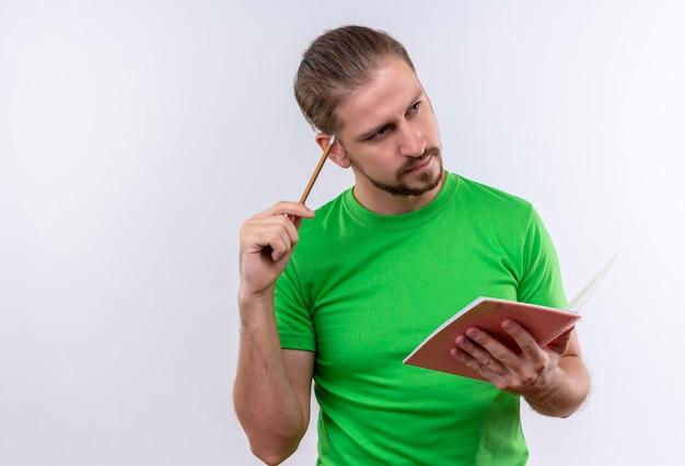 Junger schöner mann im grünen t-shirt, das notizbuch und bleistift hält, die mit nachdenklichem ausdruck auf gesicht stehen, das über weißem hintergrund steht